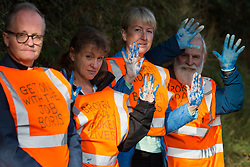 Ockham, UK. 21st September, 2021. Insulate Britain climate activists hold up their hands covered in blue paint before being arrested by Surrey Police after blocking the clockwise carriageway of the M25 between Junctions 9 and 10 as part of a campaign intended to push the UK government to make significant legislative change to start lowering emissions. Both carriageways were briefly blocked before being cleared by Surrey Police. The activists are demanding that the government immediately promises both to fully fund and ensure the insulation of all social housing in Britain by 2025 and to produce within four months a legally binding national plan to fully fund and ensure the full low-energy and low-carbon whole-house retrofit, with no externalised costs, of all homes in Britain by 2030.