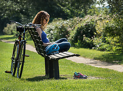 © Licensed to London News Pictures. 02/09/2017. Hampton Court, UK. A cyclist takes a break in the sunshine next to the River Thames near Hampton Court. A period of warmer weather is predicted over the next few days after the recent wet spell. Photo credit: Peter Macdiarmid/LNP