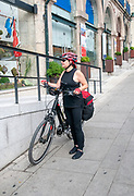Urban cycling tour concept. Woman in sport clothing and bicycle helmet with her bike. Photographed in Porto, Portugal