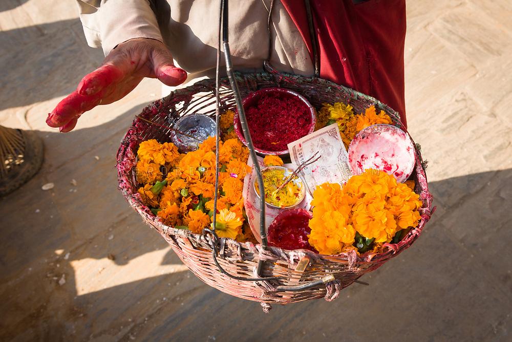 A man offers a basket of pujas (ritual offerings) in Kathmandu, Nepal. Photo © robertvansluis.com
