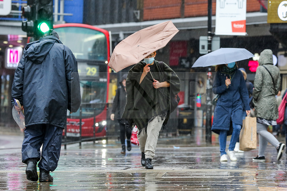 © Licensed to London News Pictures. 02/10/2020. London, UK. Members of the public shelter from rain underneath umbrellas in north London as Storm Alex arrives from Europe. The Met Office forecasts heavy rain and windy weather for the next few days in the capital, caused by Storm Alex. Photo credit: Dinendra Haria/LNP