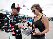 NASCAR Cup Series driver Clint Bowyer signs an autograph for a fan before a practice run at Kansas Speedway in Kansas City, Kan., Friday, May 11, 2018. (AP Photo/Colin E. Braley)