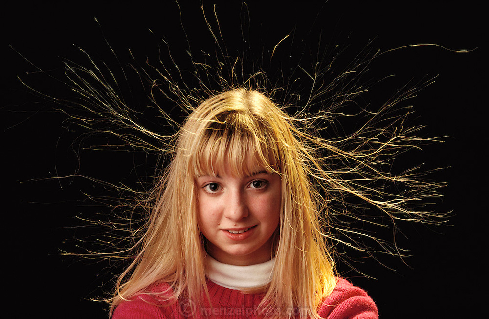 Van de Graaff generator display at the Franklin Institute in Philadelphia, Pennsylvania . Pamela Gross demonstrates static electricity. A Van de Graaff generator is an electrostatic generator used to produce a high voltage, usually in the megavolt range. Physicist Robert J. Van de Graaff invented it. The generator creates a negative charge of static electricity. When the girl touches the dome the charge passes from the dome (where it would otherwise be stored) on to her hands, and through to her hair. As the individual hairs become charged they repel each other, causing them to stand on end.  MODEL RELEASED (1991)