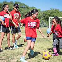 Taylor Yazzie, 9, left, and Aiyanna Lee, 6, play soccer freeze tag Thursday morning at St. Michael Indian School summer soccer Cardinal Camp in St. Michaels, Arizona.