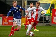 Poland's Daniel Dudzinski on the ball under pressure form Scotland's Stuart Mckinstry (Motherwell) during the U17 European Championships match between Scotland and Poland at Firhill Stadium, Maryhill, Scotland on 26 March 2019.