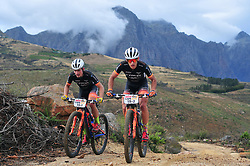 PAARL SOUTH AFRICA - MARCH 23: Stage winners Fabian Rabensteiner and Michele Casagrande summit a hill on the 70km final day, stage 7 on March 23, 2018 Wellingtion to Paarl, South Africa. Mountain bikers gather from around the world to compete in the 2018 ABSA Cape Epic, racing 8 days and 658km across the Western Cape with an accumulated 13 530m of climbing ascent, often referred to as the 'untamed race' the Cape Epic is said to be the toughest mountain bike event in the world. (Photo by Dino Lloyd)