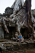 Tree root growing into the stucture of a temple in Preah Khan. Hidden deep in the jungles of Cambodia's Angkor Archaeological Park, Preah Khan is a vast temple complex sprawling across nearly 140 acres. Built by the Khmer king Jayavarman the seventh in the late twelfth century as a monastery and center for learning, it was once the heart of a city of nearly 100,000.<br /> The temple is still largely unrestored: the initial clearing was from 1927 to 1932, and partial anastylosis was carried out in 1939. Since then free-standing statues have been removed for safe-keeping, and there has been further consolidation and restoration work. Throughout, the conservators have attempted to balance restoration and maintenance of the wild condition in which the temple was discovered