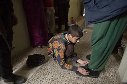 Licensed to London News Pictures. 13/02/2017. Mosul, Iraq. A young boy fastens the shoes of his father, whom is too overweight to put do it himself, after his arrest by Iraqi National Security Service officers for questioning about the location of another of his sons that may still be fighting with ISIS.<br /> <br /> The Jihaz Al-Amin Al-Watani, roughly translated as the National Security Service or NSS, are a secretive Iraqi agency that works under the responsibility of the Ministry of Interior. Since the liberation of eastern Mosul in January 2017 the NSS have been actively hunting down ISIS members who stayed behind to continue terrorism as part of sleeper cells and residents who worked with the group during its two year occupation. Recruiting from across the country agency is responsible for internal security inside Iraq and has a broad remit to investigate and arrest everything from terrorists and foreign spies to financial criminals and drug traffickers. Photo credit: Matt Cetti-Roberts/LNP