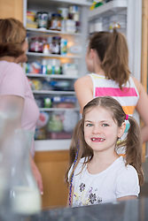 Portrait of girl, grandmother and sister looking into refrigerator in background