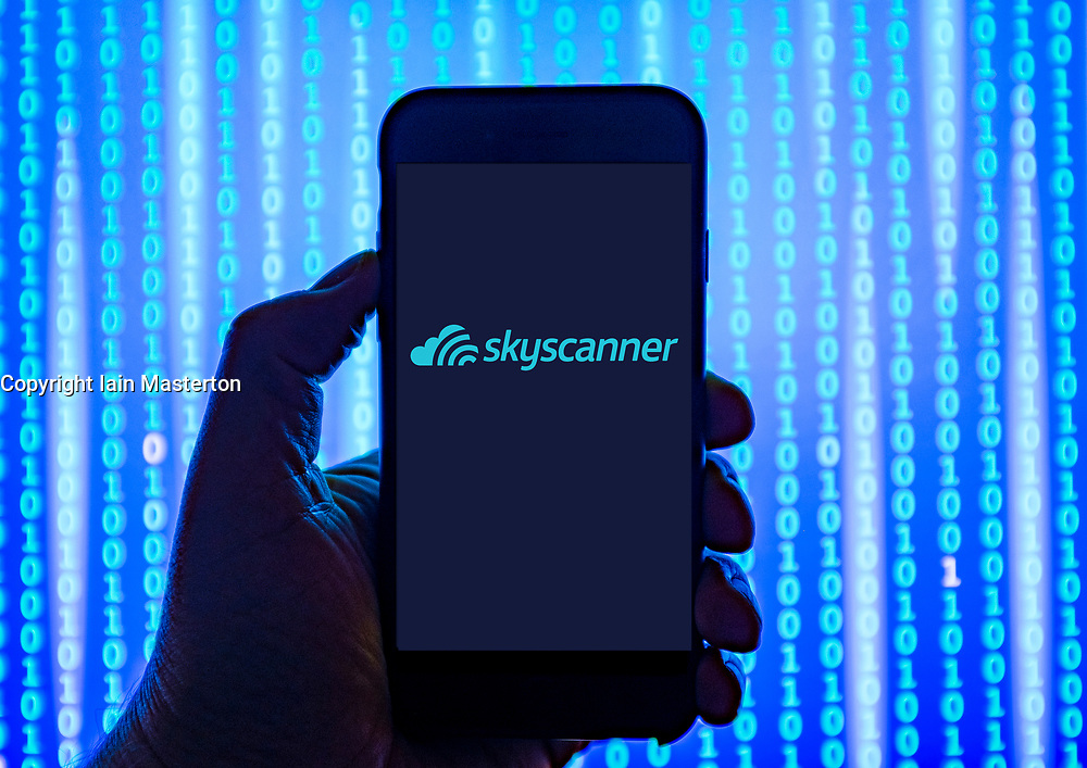 Person holding smart phone with  Skyscanner online travel booking website    logo displayed on the screen. EDITORIAL USE ONLY