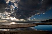 A beachgoer watches the sun peek through the clouds after a rain storm at Monarch Beach in Dana Point, CA.