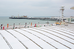"© Licensed to London News Pictures. 18/03/2018. Brighton, UK. Brighton's Palace Pier and surrounding buildings are covered in a layer of snow as a second ""Beast from the East"" is hitting the South Coast. Photo credit: Hugo Michiels/LNP"