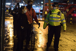 A Metropolitan Police officer uses coronavirus restrictions to ask environmental activists from HS2 Rebellion attending a candlelit vigil for the trees to be lost for the HS2 high-speed rail project in Euston Square Gardens to vacate the area on 6 February 2021 in London, United Kingdom. The vigil took place alongside the site of a tunnel in Euston Square Gardens from which bailiffs contracted to HS2 Ltd have been trying to evict nine activists seeking to protect the trees for the past eleven days and also marked the first anniversary of the death of environmental activist Iggy Fox.