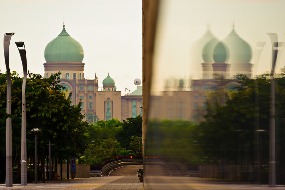 Stock photograph of the Prime Minister's Office in Putrajaya, Malaysia. The image shows the green dome reflected on the polished granite of the Ministry of FInance Building.