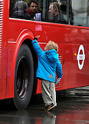 © Licensed to London News Pictures. 16/12/2011, London, UK.  2 year old Thomas Vankataolen touches the bus wheels. The first bus designed specifically for London arrived in the capital today, carrying the Mayor of London BORIS JOHNSON. The bus design is based on the famous red route master buses with a rear platform for access. Photo credit : Stephen Simpson/LNP