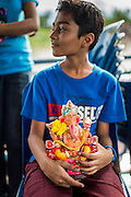 "15 SEPTEMBER 2013 - BANGKOK, THAILAND:  A Hindu boy in Bangkok holds a small statue of Ganesha on the last day of Ganesha Chaturthi celebrations at Shiva Temple in Bangkok. Ganesha Chaturthi is the Hindu festival celebrated on the day of the re-birth of Lord Ganesha, the son of Shiva and Parvati. The festival, also known as Ganeshotsav (""Festival of Ganesha"") is observed in the Hindu calendar month of Bhaadrapada. The festival lasts for 10 days, ending on Anant Chaturdashi. Ganesha is a widely worshipped Hindu deity and is revered by many Thai Buddhists. Ganesha is widely revered as the remover of obstacles, the patron of arts and sciences and the deva of intellect and wisdom. The last day of the festival is marked by the immersion of the deity, which symbolizes the cycle of creation and dissolution in nature.  In Bangkok, the deity (statue) was submerged in the Chao Phraya River.        PHOTO BY JACK KURTZ"