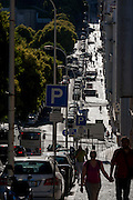 Silhouettes of pedestrians and locals on the steep street near Alameda metro station, Lisbon, Portugal.