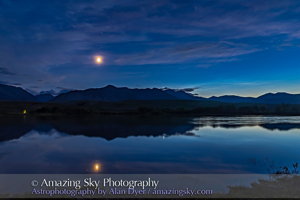 """The waxing crescent Moon, and Venus (just above the mountain ridge) and, to the right, noctilucent clouds glowing low in the north over the Waterton River at the Maskinonge picnic area in Waterton Lakes National Park, Alberta on June 17, 2018. The Moon is beside Regulus in Leo.<br /> <br /> There was no wind this night, rare for Waterton. <br /> <br /> This is a high dynamic range stack of 5 exposures from dark to light, blended with Adobe Camera Raw. Taken with the Nikon D750 and Sigma 20mm lens. Additional contrast enhancement applied using Zone System Express 5 Photoshop extension and """"Enhanced Contrast"""" function."""