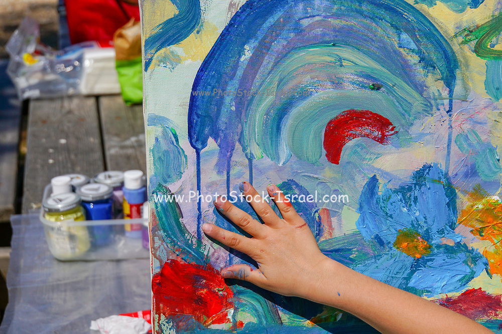 Hand of a child as he finger paints on canvas