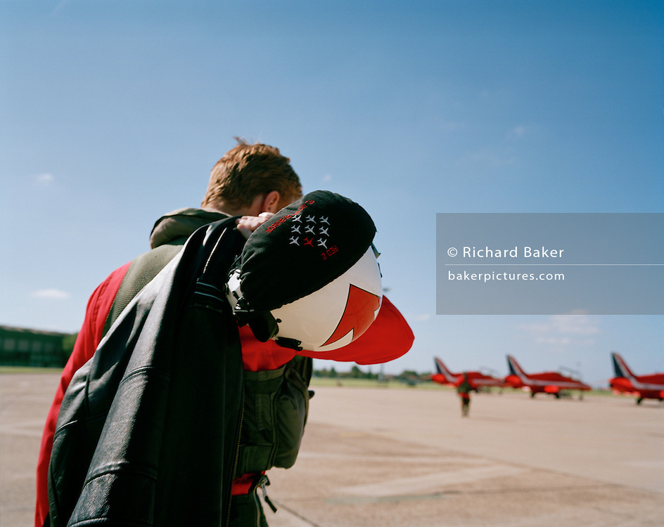 In the mid-day heat, Flt. Lt. Anthony Parkinson is a member of the elite 'Red Arrows', Britain's prestigious Royal Air Force aerobatic team. Here he walks out alone to his aircraft, which is lined up with some of the others jets at RAF Akrotiri, Cyprus before flying out to Marka in Jordan for the first display of the year. The Red Arrows arrive each April to fine-tune their air show skills in the clear Mediterranean skies and continue their busy display calendar above the skies of the UK and other European show circuit. We see John Green carrying his flight bag and life-vest over his shoulder. He paces confidently across the bright 'apron' dressed in his famous red flying suit that the Red Arrows have made famous since 1965. He is alone and striding confidently towards the matching red eight Hawk airplanes.