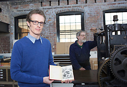 Duncan Milne of the Mehew Collection holding a first illustrated edition of Treasure Island worth up to £13,000 with the etching press used to print an map in it 1886 in the new Edinburgh Printmakers studio, opening in April. Pic copyright Terry Murden @edinburghelitemedia