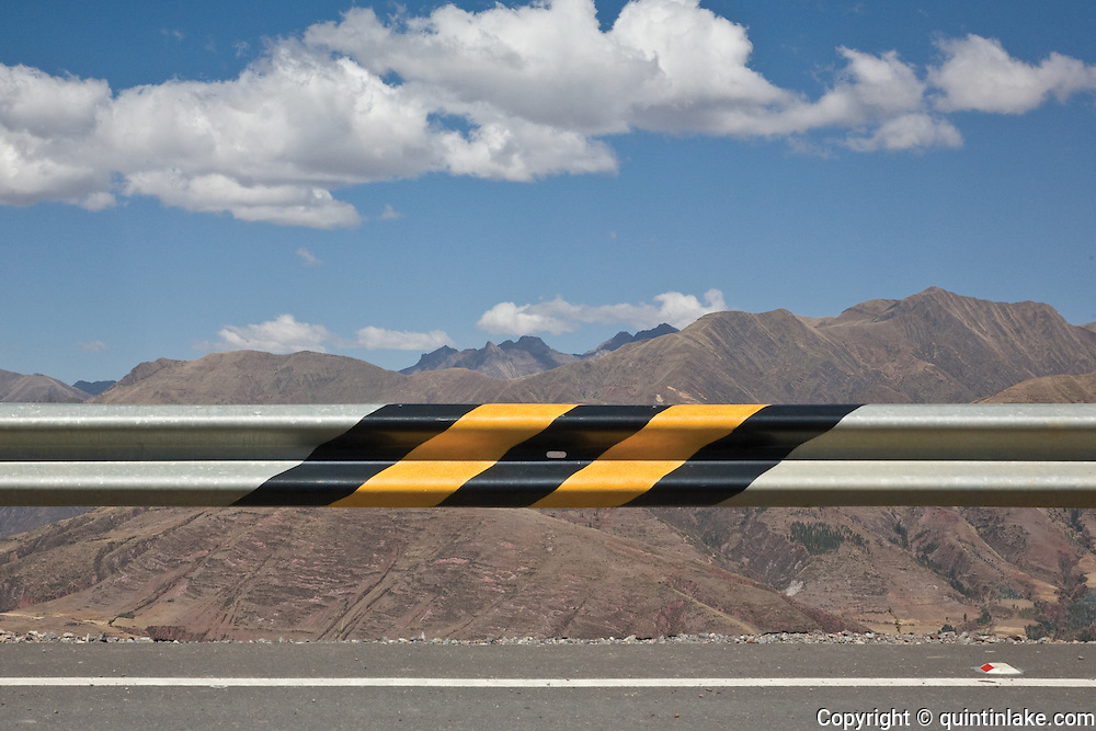 Road barrier above a steep drop at the edge of a newly completed section of the Interoceanic Highway in the Peruvian Andes. Above Cuzco, Peru, 2008