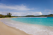 A beautiful Caribbean beach scene with clear blue waters, blue sky, and warm sand