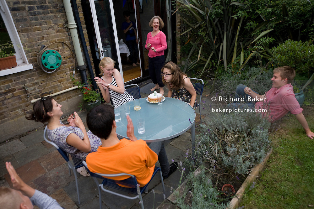 Surrounded by as few friends, a 15 year-old teenager blows out her candles brought out by her mother, in a London back garden.