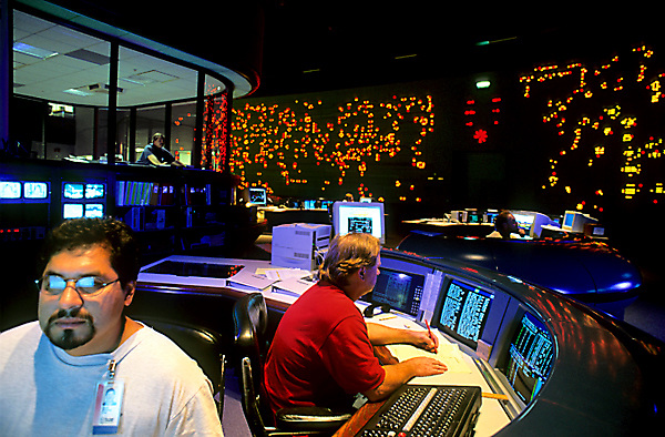 Stock photo of two men at desks monitoring vital statistics