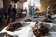 Pedestrians pass by mounds of large dried dates on sale at a market stall in a dark, busy street in Fes El-Bali, Morocco on October 31, 2007.