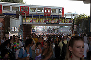 Tube travels over Portobello Road as crowds gather in Notting Hill Carnival on 25th August 2019 in West London, United Kingdom. A celebration of West Indian / Caribbean culture and Europes largest street party, festival and parade. Revellers come in their hundreds of thousands to have fun, dance, drink and let go in the brilliant atmosphere. It is led by members of the West Indian / Caribbean community, particularly the Trinidadian and Tobagonian British population, many of whom have lived in the area since the 1950s. The carnival has attracted up to 2 million people in the past and centres around a parade of floats, dancers and sound systems.