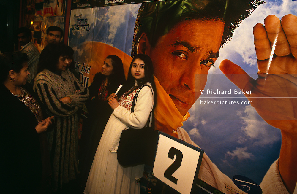 On a night out with friends, a group of five ladies are queuing for screen 2 in a Croydon cinema, South  London to see a Bollywood romantic film. On a poster behind, a giant movie hero's face looks towards the viewer with a hand raised in a salute. The man is of a dashing, handsome character  whose dark skin looks like a tanned European person. The women are in good spirits before their favourite film and gather together in the cinema's foyer in expectation. One lady is dressed in a long, smart dress and is staring with wide open eyes. She has a large handbag over the left shoulder and her long hair is spilling down her back....