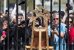 Tourists and photographers take pictures of a notice on an easel in the forecourt of Buckingham Palace in London to formally announce the birth of a baby boy to the Duke and Duchess of Cambridge at St Mary's Hospital.