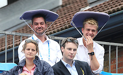 Fans protect their heads from the rain during day six of the 2017 AEGON Championships at The Queen's Club, London.