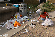 The morning after Saturday night crowds of young peoples' nightlife beach parties, their litter and rubbish from the night before stretches across the coastal paths and shingle, a local volunteer picks up and bags up piles of litter along the sea wall, on 19th July 2020, in Whitstable, Kent, England.  The volunteers and a council cleaner come every morning to clean-up the mess left by others which, they say, has got worse during the Coronavirus pandemic lockdown and now, the slow easing of health guidelines.