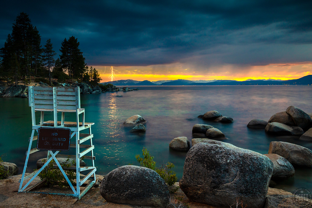 """""""Lightning at Lake Tahoe 1"""" - Photograph of a lightning strike at Lake Tahoe, shot from the lifeguard chair at Sand Harbor, shortly after sunset."""