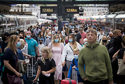© Licensed to London News Pictures. 31/07/2021. London, UK. Members of the public, some not wearing face masks, disembark a train at Kings Cross Station in central London. The UK's COVID-19 cases continue to fall following the removal of restrictions on July 19th. Photo credit: Ben Cawthra/LNP