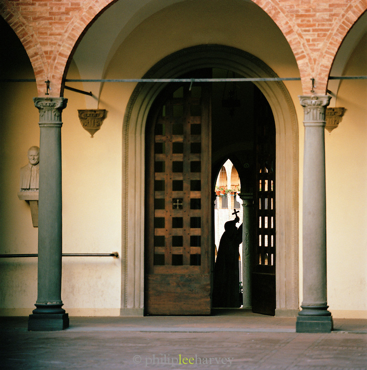 Sculpture of a man holding cross in the doorway of a church, Siena, Italy