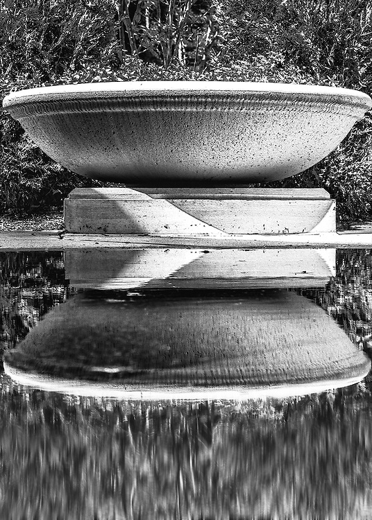 A large stone planter casting a reflection in the rain water puddle on the ground