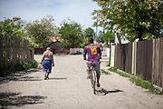 "A man with a ""Ronaldinho"" jersey is cycling one of the main streets in the Roma area of Frumusani."