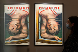 """© Licensed to London News Pictures. 24/09/2021. LONDON, UK. A staff member views a vintage poster of """"Harry Houdini Upside Down in The Water Torture Cell"""", printed c.1913-15, (Est $40,000-60,000). Preview of a collection spanning the history of magic from celebrity magician Ricky Jay.  The works are being shown in Sotheby's, New Bond Street, ahead of their auction in New York on 27 and 28 October.  Photo credit: Stephen Chung/LNP"""
