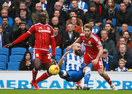 Brighton defender Bruno Saltor takes a tumble after pressure from Middlesbrough FC midfielder Albert Adomah during the Sky Bet Championship match between Brighton and Hove Albion and Middlesbrough at the American Express Community Stadium, Brighton and Hove, England on 19 December 2015. Photo by Bennett Dean.