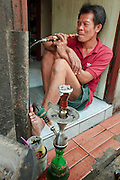 "Mar. 19, 2009 -- BANGKOK, THAILAND: A man smokes a water pipe in the doorway of his home in the Ban Krua section of Bangkok. The Ban Krua neighborhood of Bangkok is the oldest Muslim community in Bangkok. Ban Krua was originally settled by Cham Muslims from Cambodia and Vietnam who fought on the side of the Thai King Rama I. They were given a royal grant of land east of what was then the Thai capitol at the end of the 18th century in return for their military service. The Cham Muslims were originally weavers and what is known as ""Thai Silk"" was developed by the people in Ban Krua. Several families in the neighborhood still weave in their homes.   Photo by Jack Kurtz"