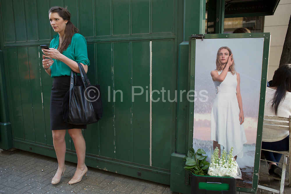 Photograph of a model in a summer dress interacting with passer by at the Stella McCartney flower stall on New Bond Street, London, UK.