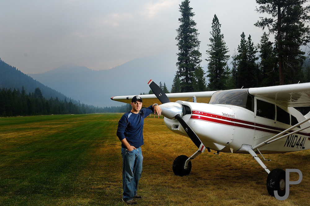 Adam Pratt in front of Maule M7-235C airplane at Johnson Creek, ID.  Smoke from forest fires in background.