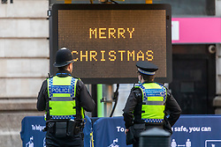© Licensed to London News Pictures. 22/12/2020. London, UK. Police patrol Victoria Station as commuters and travellers are greeted with a Merry Christmas sign in an almost empty Victoria Station in London this morning. Yesterday a huge rush of shoppers descended on store causing long queues in the aisles and empty shelves after news that French customs blocked freight from Dover to France after a spike in infections due to the Covid-19 mutation. Last week Prime Minister Boris Johnson put London and parts of the South East into Tier 4 lockdown after the new Covid-19 mutation was discovered. Photo credit: Alex Lentati/LNP