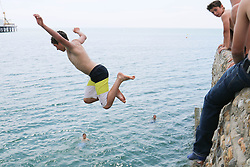 © Licensed to London News Pictures. 25/07/2014. Brighton, UK. Kids jumping of the jetty in to the sea in Brighton. The weather is expected to reach temperatures around the 25C in Brighton and the South Coast. Photo credit : Hugo Michiels/LNP