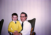 Young boy wearing yellow jumper and  sits on his father's knee at home, British culture 1967