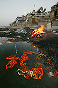 A man dries the clothes he just washed in the Ganges in the heat of a burning funeral pyre at the Harishchandra cremation grounds. The Harishchandra Ghat (also known as the Harish Chandra Ghat) is the smaller and more ancient of the two primary cremation grounds in Varanasi, on the banks of the Ganges River.