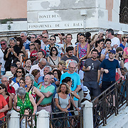 VENICE, ITALY - JULY 19: Venetians and Tourist watch from the bank of Giudecca Canal the opening of the votive bridge to the Redentore Church on July 19, 2014 in Venice, Italy. Redentore , which is in remembrance of the end of the 1577 plague, is one of Venice's most loved celebrations. Highlights of the celebration include the pontoon bridge extending across the Giudecca Canal, gatherings on boats in the St. Mark's Basin and a spectacular fireworks display.  (Photo by Marco Secchi/Getty Images)